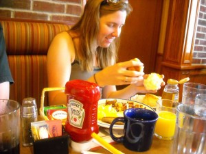 Sam eats breakfast surrounded by a wall of condiments.